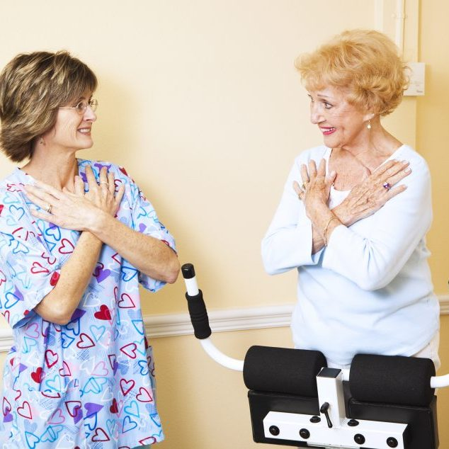 Senior woman at chiropractors office, working with a physical therapist to learn exercises for her back problems.